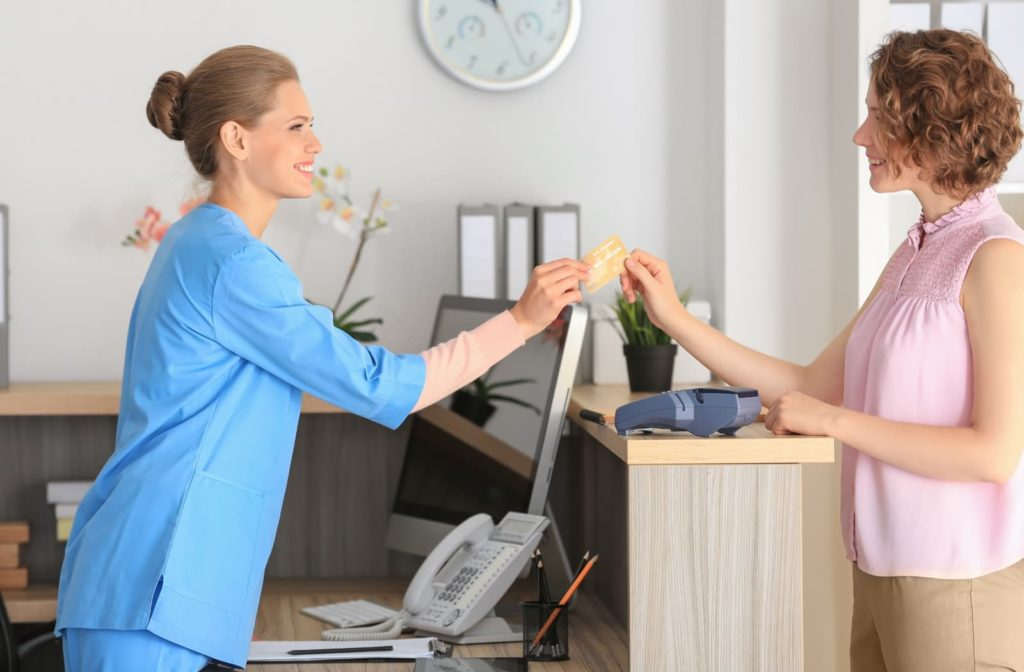 Dental receptionist taking payment for dental services from a woman