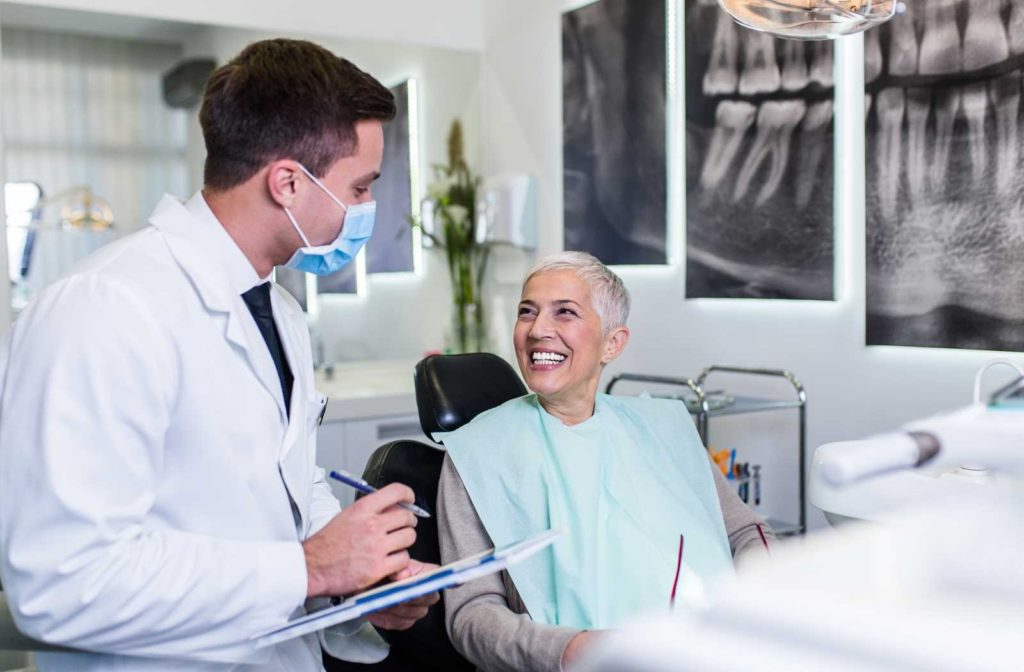 beautiful senior woman talking to a male dentist in white from the dentists chair.