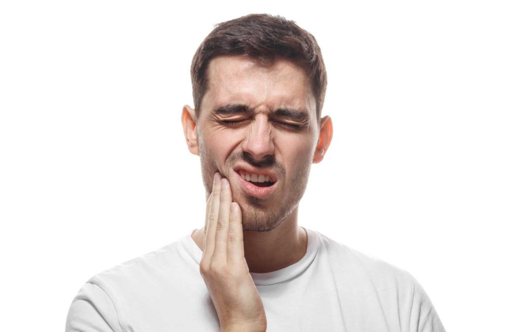 Man on white background holding jaw and squinting in pain from sensitive teeth
