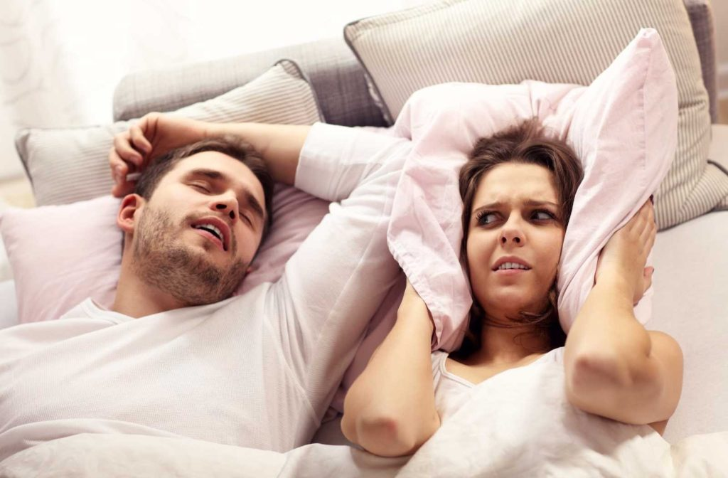 married couple struggling with husband's sleep apnea on white sheets with warm filtered lighting