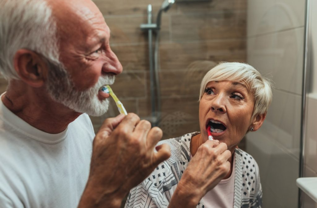 A senior couple brushing their teeth together.
