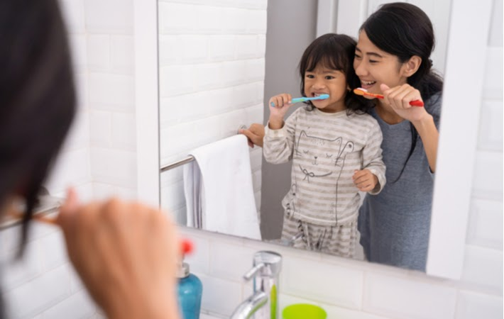 Mother and daughter brushing their teeth before bed.