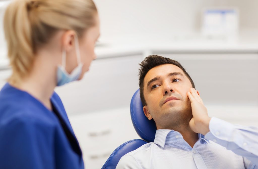 Young man at dentist office explaining tooth pain to his doctor.