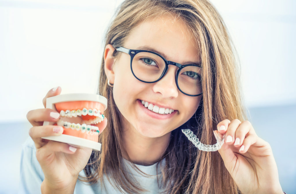 Young girl holding teeth model with braces on and Invisalign on the other hand.