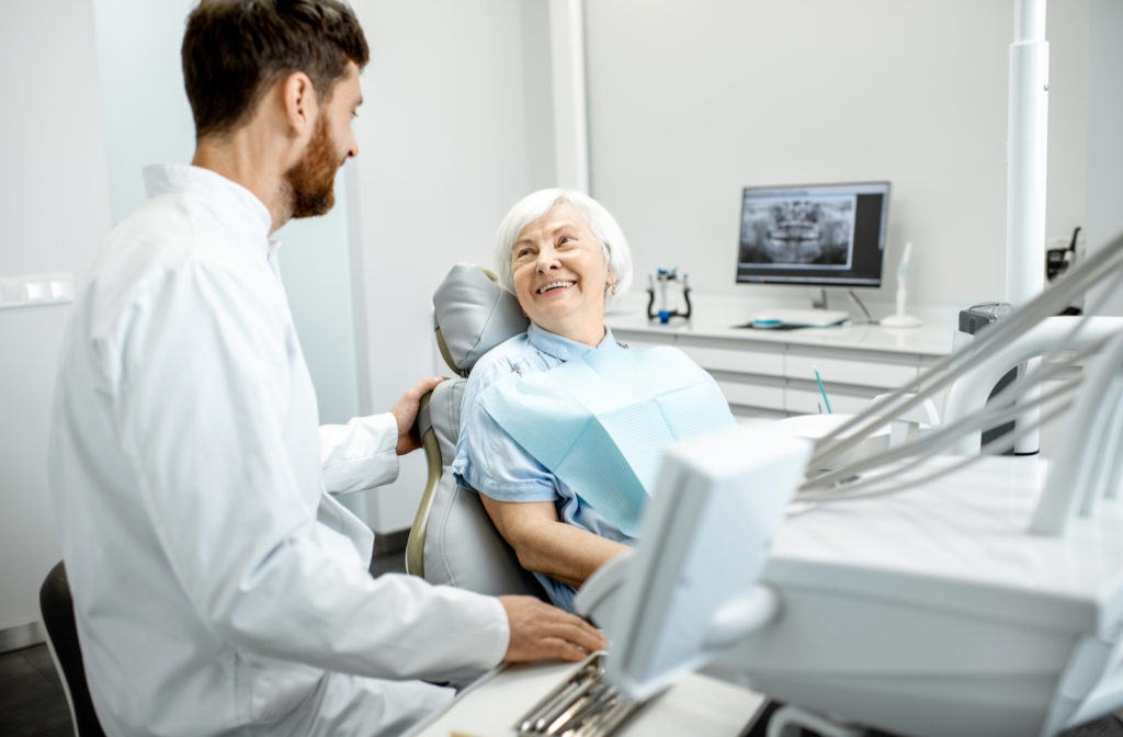 Dentist talking to patient during exam at clinic