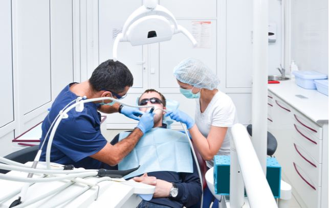 Man undergoing dental surgery by dentist and dental assistant at clinic